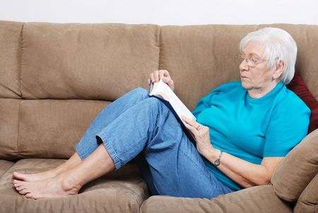 woman on couch: Senior Woman Falling A Sleep While Reading Book