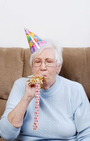 Senior Woman With Birthday Hat Blowing A Noise Maker photo