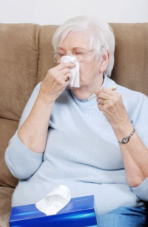 sick senior with thermometer blowing her nose photo