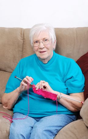 woman on couch: happy senior knitting Stock Photo