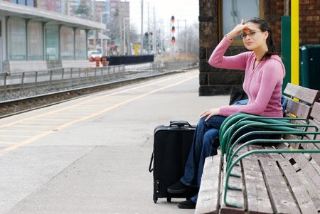 woman sitting on bench looking for the train photo