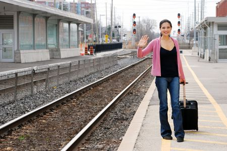 woman with luggage waving at train station photo