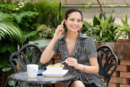 young woman talking on a cell phone over lunch