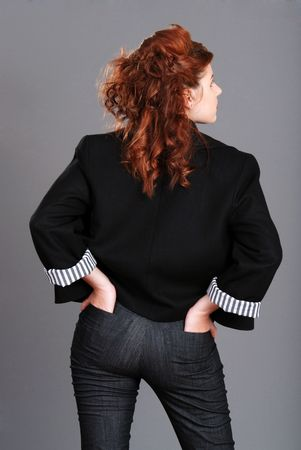 hands behind head: red head woman with hands in back pockets Stock Photo