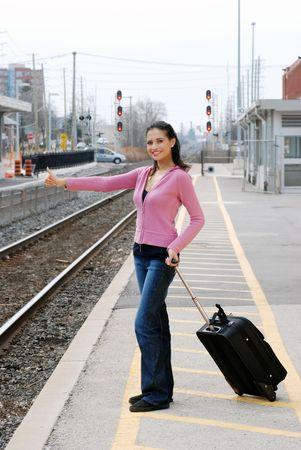 woman hitchhiking at railroad station photo
