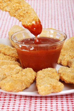 suppertime: dipping chicken finger in BBQ sauce Stock Photo