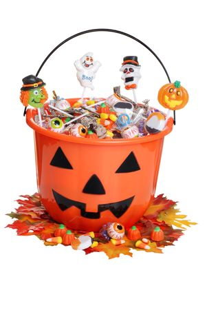 child halloween pumpkin bucket with candy and fall leaves Stock Photo