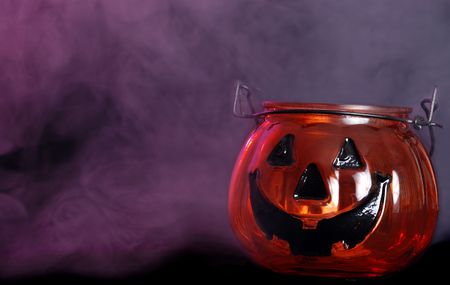 candle holder: glass halloween pumpkin candle holder with smoke Stock Photo