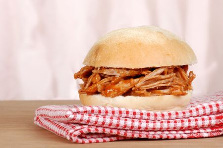 sloppy: closeup barbecue pulled pork sandwich