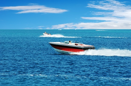 red power boat with blue sky and clouds