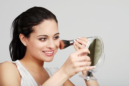 ヒスパニックの女性彼女の化粧を置く