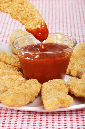 chicken fingers: dipping chicken finger in BBQ sauce Stock Photo