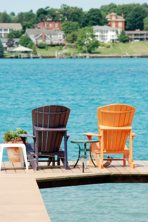 brown and orange adirondack chairs on a dock photo