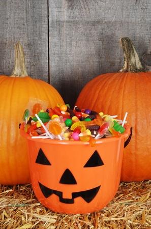 fruit worm: candy filled halloween pumpkin bucket Stock Photo