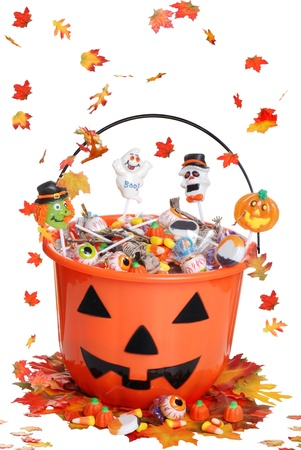 halloween skeleton: halloween pumpkin bucket with candy and falling  leaves Stock Photo