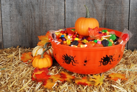halloween decoration: bowl of halloween candy with fall leaves