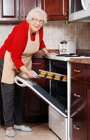 baking tray: senior woman baking cookies