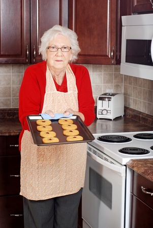 baking tray: senior woman with fresh baked cookies