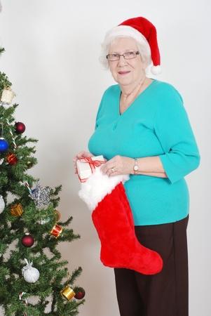 holding a christmas ornament: Senior woman filling christmas stocking Stock Photo