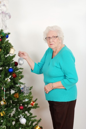 great grandmother: Senior woman hanging christmas ornament Stock Photo