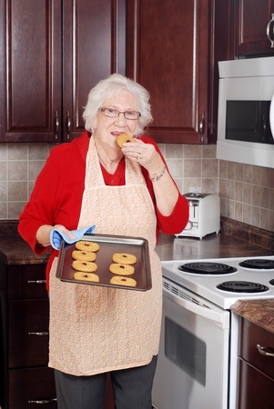 senior woman eating fresh cookie photo
