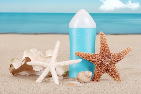 Suntan lotion with shells on the beach photo