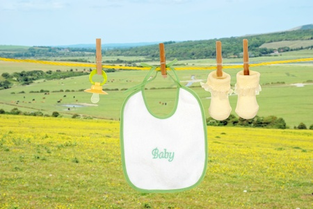 Baby bib socks and pacifier on clothes line photo