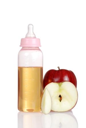Pink baby bottle with fresh apple juice photo