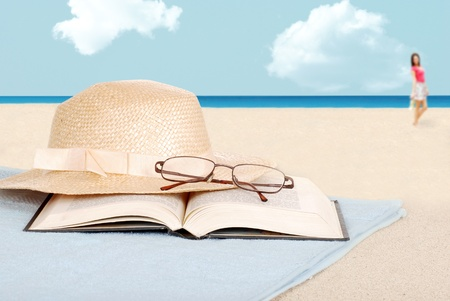 book: book glasses and hat on the beach