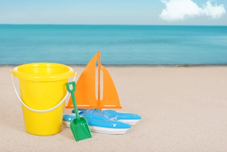 Toy Sailboat and childs bucket on the beach Stock Photo - 12783309