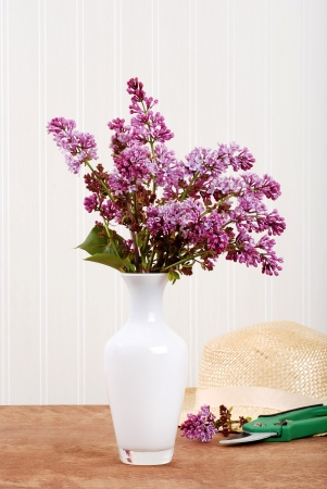 Fresh cut lilac with straw hat Imagens