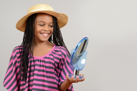 young black girl trying on straw hat photo