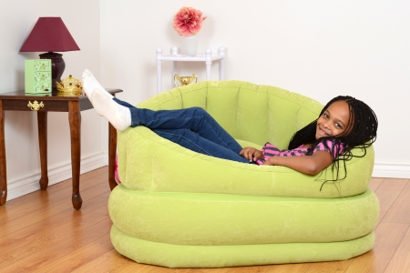 cornrows: South African child relaxing in green chair Stock Photo