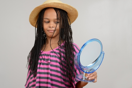 cornrows: Young Black girl looking in mirror