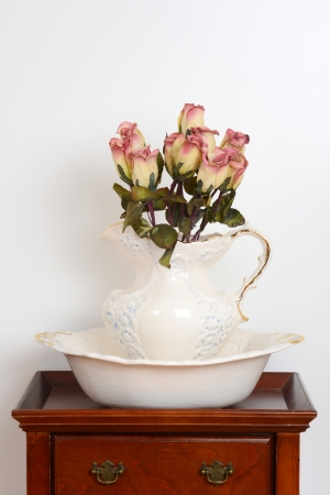 Old bowl and jug on a stand with fake roses photo
