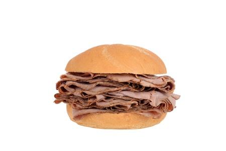 french bread rolls: Large roast beef on a bun sandwich