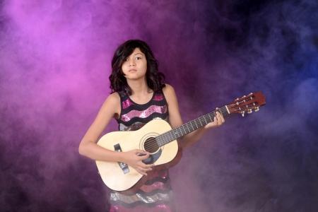 Woman beat guitar: Cô gái trẻ chơi guitar trên sân khấu