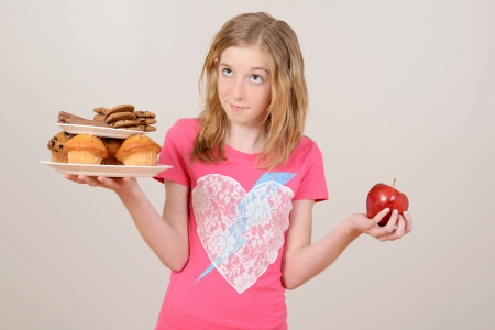 Young girl deciding junk food or apple photo
