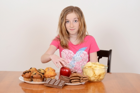 deciding: child picking healthy apple over junk food