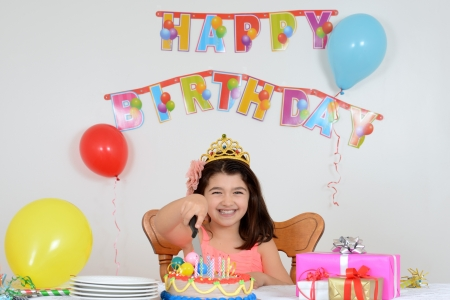 children party: happy child cutting birthday cake