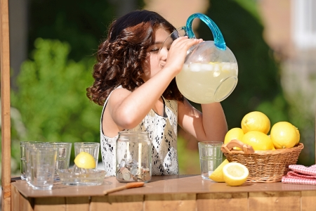little girl drinking from lemonade pitcher photo
