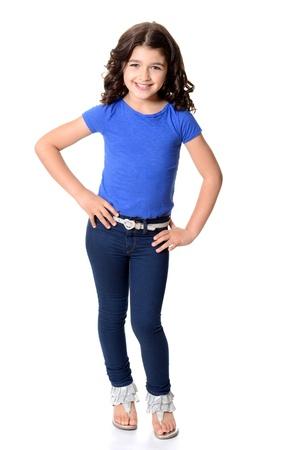 klein meisje draagt blauwe jeans met handen op de heupen