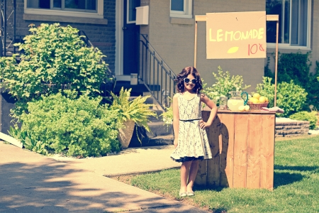 retro girl wearing sunglasses with lemonade stand photo