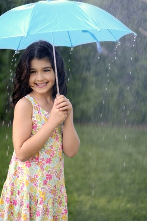 jong meisje spelen in de regen met paraplu Stockfoto