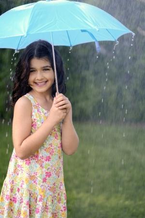 mojar: niña jugando en la lluvia con paraguas