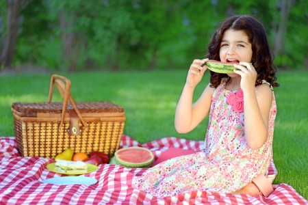 child with slice watermelon at picnic photo