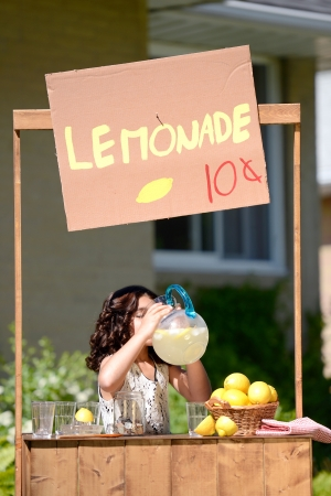 fruit stand: girl drinking lemonade from a pitcher Stock Photo