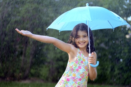 kids playing water: young girl enjoying the rain