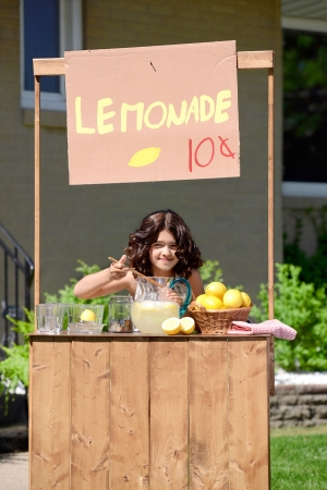 sell: young girl making lemonade at her stand