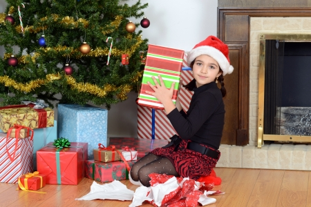 young girl shaking christmas gift photo